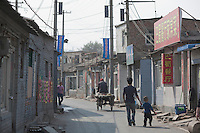 Residents walk through a road at Dawangjing Village which is being demolished on April 9, 2009 on the outskirts of Beijing, China. The local authorities are evicting residents, who are mainly migrant workers, to redevelop the area. The redevelopment of Beijing continues in high speed.