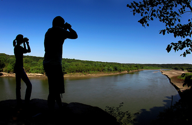 Jenni Dyar, left, and Billy Reiter-Marolf of the Iowa DNR look through their binoculars while birdwatching from a ledge above the Des Moines River at Ledges State Park.