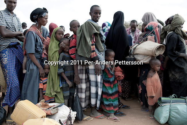 DADAAB, KENYA - JULY 29: Unidentified newly arrived Somali refugees wait to register with UNHCR in the IFOR refugee camp on July 29, 2011 outside Dadaab, Kenya. Hundreds of thousands of people have fled the hardship and civil war in Somalia to Dadaab. A severe drought has added to the misery and hardship. Some refugees has walked for up to thirty days to reach the camp, and some children died on the way, due to lack of food and water. (Photo by Per-Anders Pettersson)