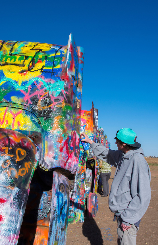 Amarillo Texas famous Cadillac Ranch teen spraying paint off of Route 66 old Cadillacs buiried in ground on Rt 66   9