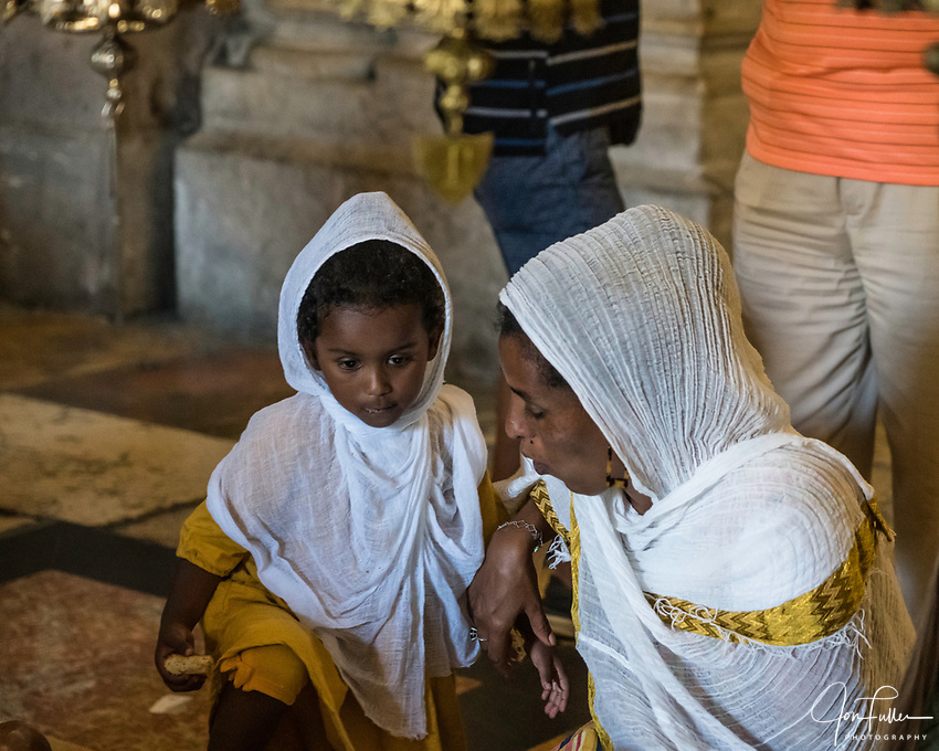 A young Ethiopian Christian pilgrim and her mother visiting the Church of the Holy Sepulchre in the Christian Quarter of the Old City of Jerusalem.  The Old City of Jerusalem and its Walls is a UNESCO World Heritage Site.  This church was built over the site believed by many to be location of the death and burial of Jesus Christ.