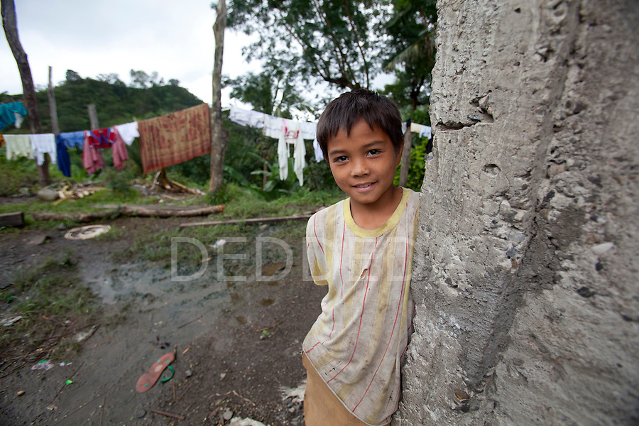 A young Filipino boy smiles for the camera at his modest home in a rural area near the Twin Lakes National Park on Negros Island, Philippines.