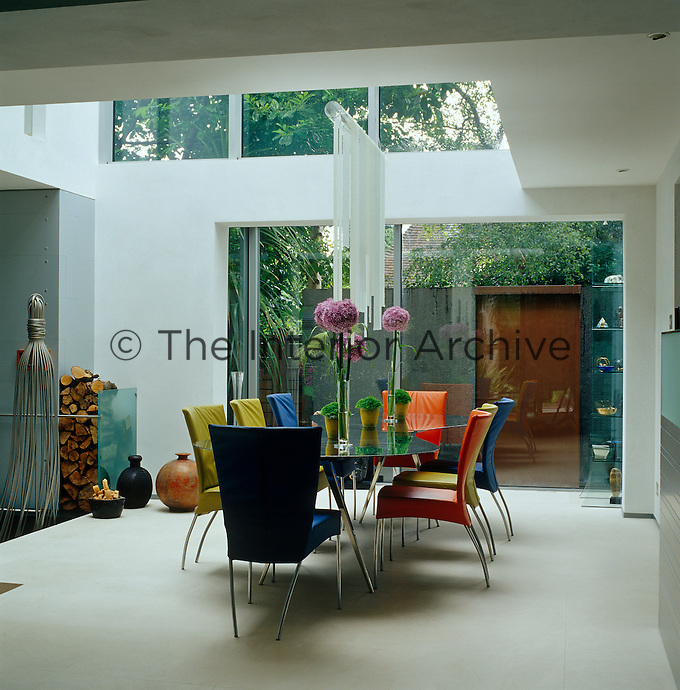 Multi-coloured chairs surround a metal dining table by Ron Arad in this double-height dining room