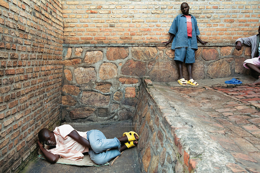 Rwanda. Southern province. District of Muhanga. Central jail of Gitarama. Minors block. A black boy lays on the ground while another teenager stands close to the bricks wall. Behind bars. Minors in detention. Detention pending trial and after trial, when sentenced to prison. The non-governmental organization (NGO) Fondation DiDé - Dignité en détention runs the Encademi (Encadrement des mineurs) program. Prison centrale de Gitarama. Quartier des mineurs.  © 2007 Didier Ruef