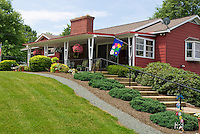 Entrance curb appeal front porch house plantings with steps, mulch, evergreen Juniperus groundcovers, container pot of Calibrachoa, flag, red house, driveway, garage, stone wall, sloped hillside property, blue skies, rhododendron shrubs, lawn grass, in sun with blue skies, wide view