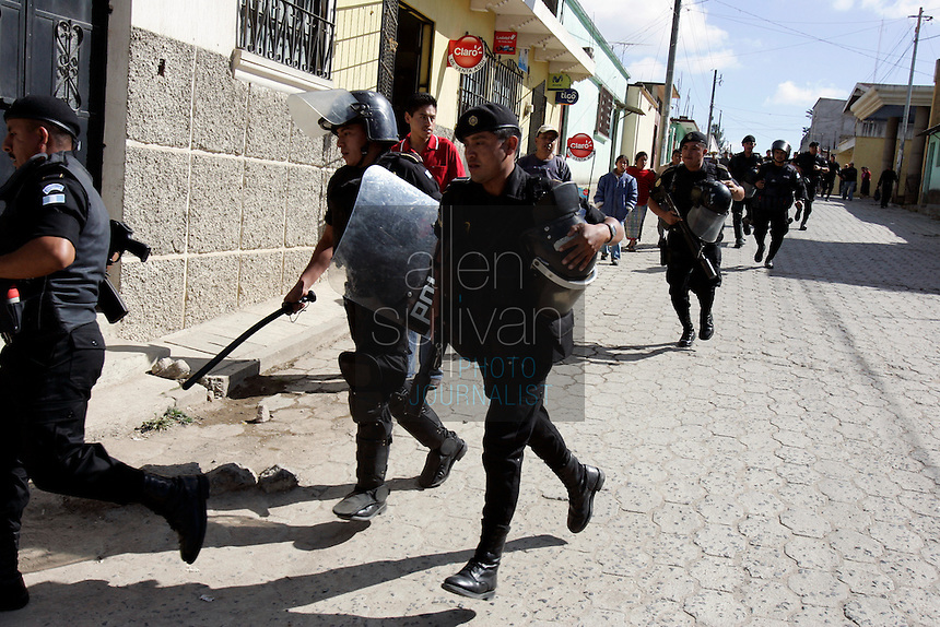 Police run to help others contain protests by indigenous people against U.S. President Bush in Tecpán Guatemala, Guatemala. Bush visited a nearby Mayan site, Iximché.