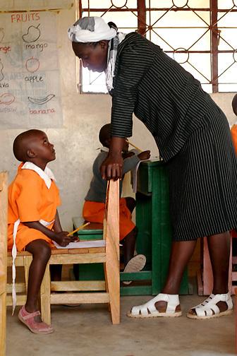 Fidy Ntinyari and her teacher, Albina Ngugi, discuss the yearly final at the Early Childhood Development school at Pepo La Tumaini Jangwani, a community based HIV/AIDS program in Isiolo, Kenya., on Tuesday, July  29, 2008.  (Photo by Bryce Yukio Adolphson, © 2008)