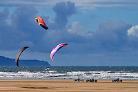 Westward Ho! in North Devon, the only town in Britain with an exclamation mark in its name boasts a spectacular long and very flat beach. Windswept by the prevailing westerly winds it is a popular venue for kite surfing, kite boarding and kite buggying (shown here). On Saturday mornings the local club organises kite buggy races up and down the vast beach, which is always a great photo opportunity. Here three racers are heading south along the beach, their colourful parafoils overhead. Behind lies Hartland Point, with its lighthouse just visible near sea level, and the domed Ministry of Defence radar tower on top of the cliffs.