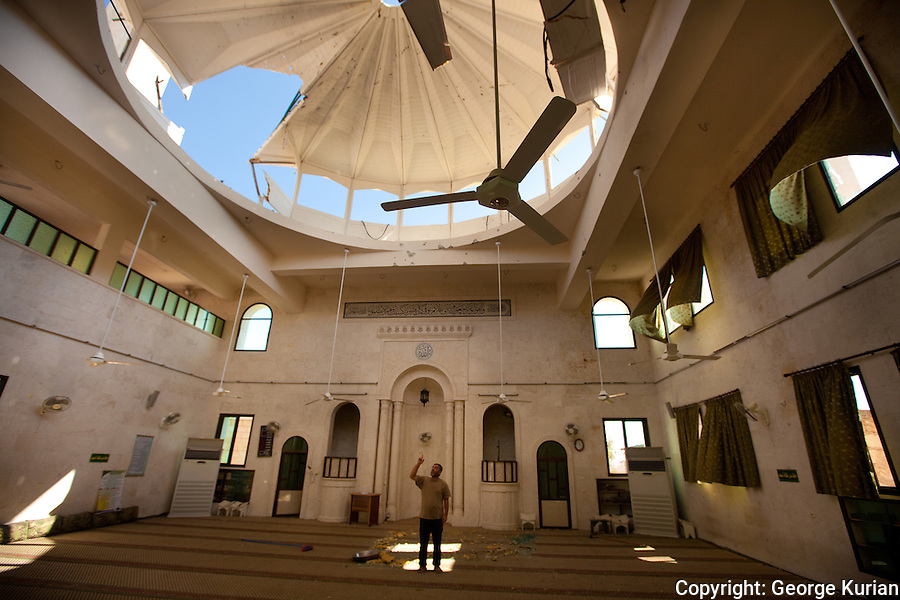 02/08/20l2: Ahmed Maroof of Anadan explains how Anadan was attacked by jets, helicopters, tanks and artillery fire. Here he is inside the devastated Anadan mosque pointing to the dome, shot through by artillery fire. 90% of Anadan's residents have fled the town, following the attack, he claims.