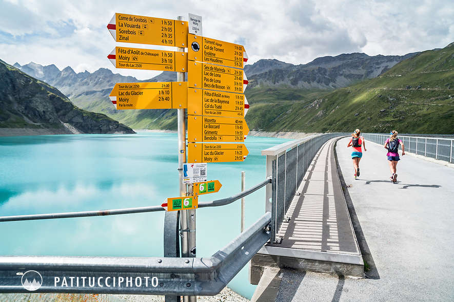 Two women run by a trail sign on the dam at Lac de Moiry, Switzerland