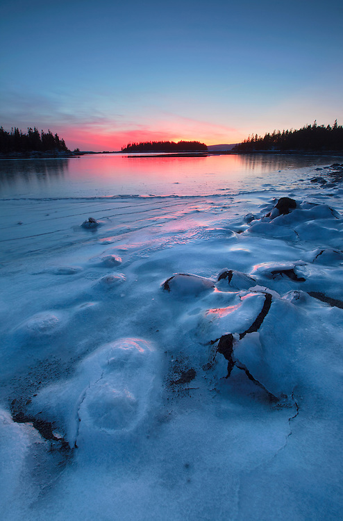 A sheet of ice covers the boulders in West Pond Cove during frigid weather and a fiery sunset on the Schoodic Peninsula, Acadia National Park, Maine, USA