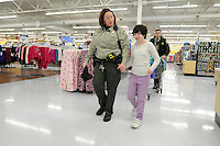 NWA Media/ J.T. Wampler - Amanda Arnold, a sergeant with the Washington County Sheriff's office, helps Deja Sorrell of Greenland shop Friday Dec. 5, 2014. The department's Shop With A Cop program provides selected children from area school districts with an all expense paid shopping trip with a uniformed officer for clothes, toys and more.