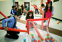 NWA Democrat-Gazette/DAVID GOTTSCHALK Students in Missy Weber's pre-k education class, including Jaylah Aguilar (from right) and Aaliyah Silva, play noodle hockey Wednesday, February 14, 2018, during Stretch and Grow at the Springdale Early Childhood Center. Early education options are steadily increasing as Northwest Arkansas' population grows and people want more choices.