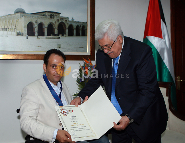 Palestinian President, Mahmoud Abbas (Abu Mazen)  honors Osama Silwadi the Medal Of Merit and Excellence, in the West Bank city of Ramallah, on June 14, 2012. Photo by Thaer Ganaim
