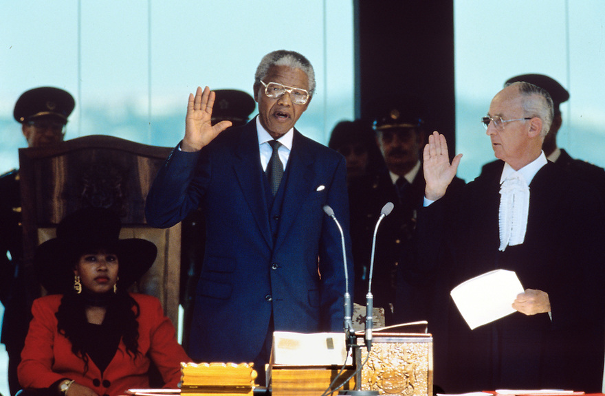 Nelson Mandela's raises his hand to take the oath of office at his  inauguration as President of South Africa.  After more then 27 years in jail as an anti-apartheid activist,   Nelson Mandela lead a 1994 campaign for President as a member of the African National Congress (ANC),  in the first free elections in South Africa in 1994.  Mandela has received more than 250 awards over four decades, including the 1993 Nobel Peace Prize.