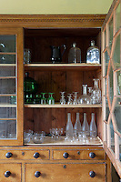 A substantial kitchen cupboard displays a collection of glasses, bottles, and storage jars