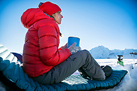 A woman sits on a sleeping pad drinking a hot drink while snow camping