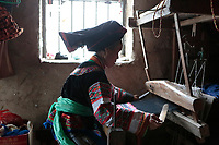 A Bouyei woman weaves a piece of Brocade at home at Guanling Bouyei and Miao Autonomous County in Guizhou Province, 2018.