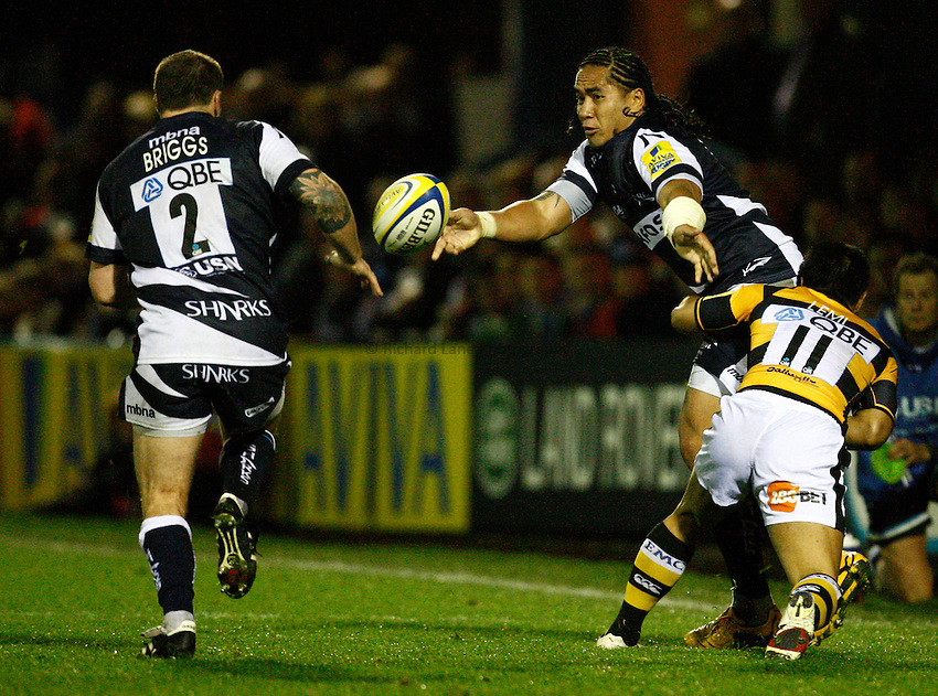 Photo: Richard Lane/Richard Lane Photography. Sale Sharks v London Wasps. Aviva Premiership. 01/10/2010. Sale's Andy Tuilagi offloads to Neil Briggs as he is tackled by Wasps' David Lemi.
