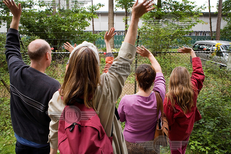 Protestors wave at prisoners in the cells of Camp Zeist (Kamp Zeist) while two guards with bullet proof vests watch from a nearby minibus with their engine running. On the first Sunday of every month, a vigil is held outside the camp in protest of the detention of illegal migrant detainees and their children.
