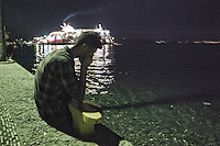 A tired refugee waits on the dock at night, hoping to take the ferry in the distance to Athens. Kos, Greece. Sept. 6, 2015