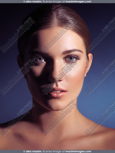 Beauty portrait of a young woman with clean natural look under artistic dramatic lighting isolated on dark blue background