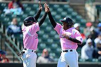 Rochester Red Wings second baseman Eric Farris #39 is congratulated by Ray Olmedo #1 after scoring a run during a game against the Columbus Clippers on May 12, 2013 at Frontier Field in Rochester, New York.  Rochester defeated Columbus 5-4 wearing special pink jerseys for Mother's Day.  (Mike Janes/Four Seam Images)