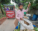 A street vender weighs his product in Suihari in northern Bangladesh.