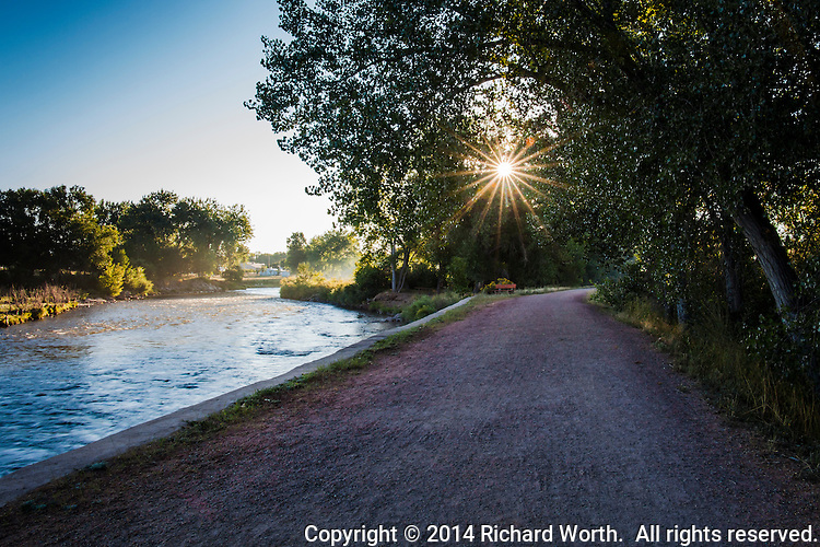 An early morning sunburst beams through the trees along the Arkansas Riverwalk in Canon City, Colorado
