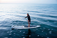 A stand up paddleboard paddler during an evening workout on Lake Superior at Grand Marais Michigan.