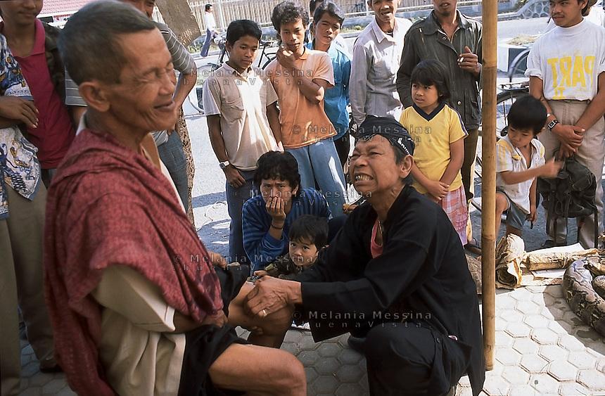 Indonesia, Java island : the Dukun (healer)Pak Iwo massages an old man to heal his pain.<br /> Indonesia, Giava: il dukun (guaritore) Pak Iwo massaggia un suo paziente per guarirlo dai dolori.