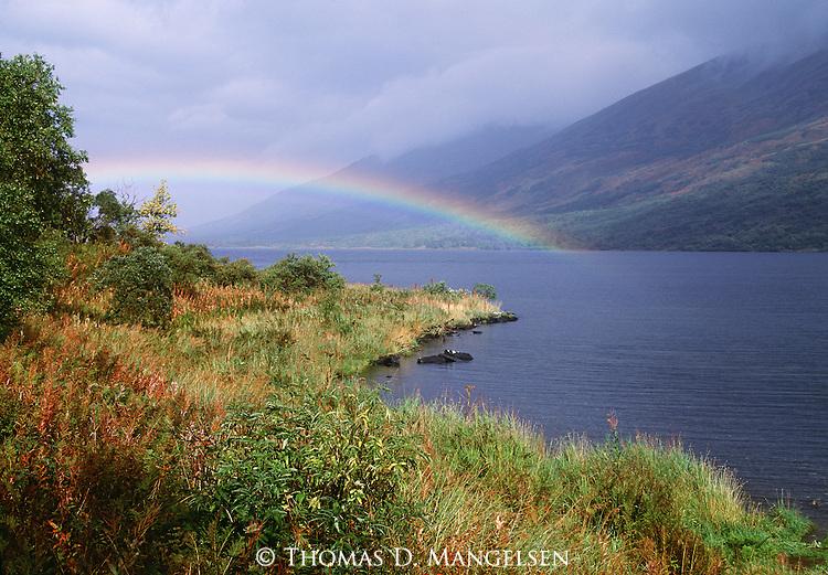 Rainbow arching over a lake in Denali National Park, Alaska.