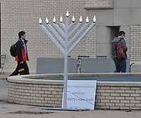 NWA Media/Michael Woods --12/23/2014-- w @NWAMICHAELW...People walk past a giant Menorah in front of the Arkansas Union on the University of Arkansas campus Tuesday afternoon in Fayetteville as Hanukkah comes to an end Wednesday evening.  The menorah was set up by the Chabad of Northwest Arkansas.