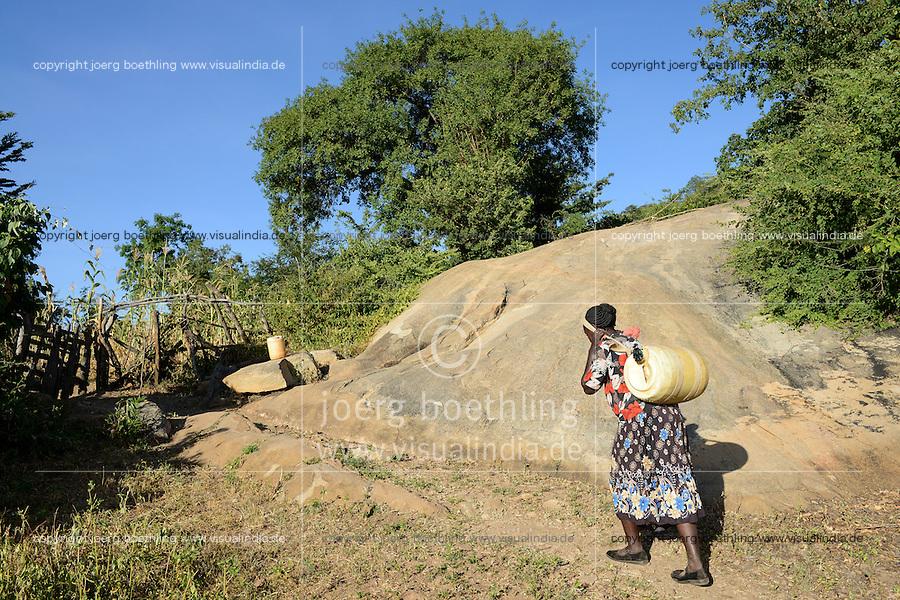 KENIA, ADS Anglican Development Services of Mount Kenya East, Stadt Embu, Dorf Gichunguri, Projekt Regenwasserauffang an einem Felsen und Speicherung in Tanks zur Nutzung in Duerreperioden, Agnes Irima, 44 Jahre, traegt einen gefuellten Wasserkanister nach Hause, ca. 200 Meter