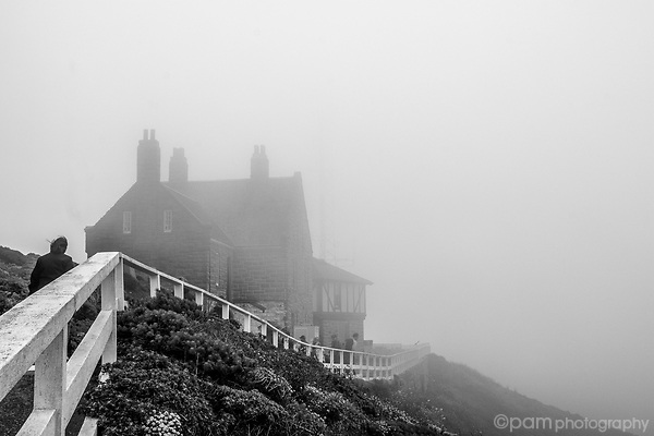 Fog over Big Sur's Point Sur's Lighthouse with person walking