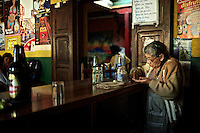 In an underworld where people go to let time go by, she works incessantly and counts the money she's made today.  ...Bar La Copa, 3a Calle Poniente #27, La Antigua, Guatemala. ..En un sub-mundo donde la gente va a pasar el tiempo, ella trabaja incesantemente y cuenta los pesos que ha hecho en la mañana de hoy.