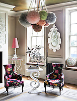 Multi-coloured net pompoms suspended from the ceiling add a further dimension to the eclectic range of objects and furniture in the entrance hall