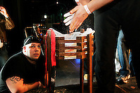 "Dan Fortuna looks on as a fellow arm wrestler applies chalk to his hands for better grip at the 28th Annual Big Apple Grapple, held in New York City on March 19, 2005.  The tournament is the first in the 2005 New York Arm Wrestling Association's ""Golden Arm Series""."