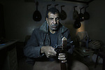 """Hammad Atwa, a Palestinian man who makes lutes, known in Arabic as an """"Oud"""", works on a musical instrument at the Khan Younis refugee camp in the southern Gaza Strip on February 19, 2014. Hammad sells his handmade lutes for 300 American dollars a piece. Photo by Eyad Al Baba"""