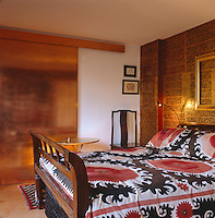 A sliding copper door separates the bedroom from the living area; the wall behind the bed is lined with pages from a Burmese bible and the bed is covered with a Susani textile