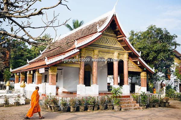 A monk walking by Vat Sop Sickharam. Luang Prabang, Laos.