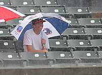 A fan seems to not mind the pouring rain during a delay before a game between the Myrtle Beach Pelicans and the Potomac Nationals on Aug. 7, 2010, at BB&T Coastal Field in Myrtle Beach, S.C. Photo by: Tom Priddy/Four Seam Images
