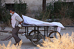 A Red Crescent worker carries a body of dead fighter loyal to Free Syrian Army on carts during an exchange of dead bodies between Free Syrian Army and Syrian Government forces, in Bustan al-Qasr district in the east of the northern Syrian city of Aleppo on June 11, 2015. Photo by Ameer al-Halbi