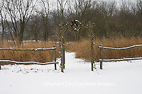 63821-19315 Rustic fence and arbor with holiday wreath & lights near prairie in winter, Marion Co.  IL