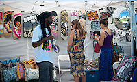 """Shoppers at the AfroPunk Festival in Commodore Barry Park in Brooklyn in New York on Sunday, August 26, 2012. The festival in the neighborhood of Fort Greene bills itself as the """"other black experience"""" and blends the black punk and hardcore punk scenes. There is also a diverse aspect combining other minority groups, all dressed in their fashionable punk ensembles. (© Richard B. Levine)"""