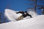 Male snowboarder making snowy turns down Outer Limits, a double black diamond trail, Killington, Vermont.