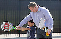 NWA Democrat-Gazette/DAVID GOTTSCHALK  Jason Ewards, assistant principal at Vandergriff Elementary School, volunteers Thursday, September 10, 2015 to help Gabe Cruz, 7, a first grade student at the school, as they participate in a Free Play Day tennis clinic on the courts at the elementary school in Fayetteville. A joint use agreement grant between the U.S. Tennis Association and Vandergriff Elementary School has allowed the school to open the courts to the public after school hours on weekdays beginning at 4:00 p.m. and all day on the weekends.