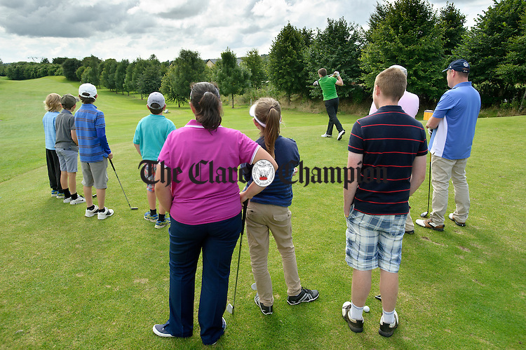 Woodstock Junior players look on as the Clare U-21 captain and Clare senior player Tony Kelly tees off at the first in the Clare Football fundraising outing. Photograph by John Kelly.