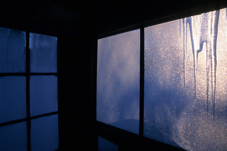 Frost clings to cabin windows framed with hanging icicles on a frigid cold morning in Anchor Point, Alaska.