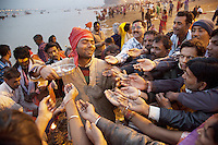 India. Uttar Pradesh state. Allahabad. Maha Kumbh Mela. At the end of a puja in Sangam, a group of Indian Hindu devotees, men and women, received food. The food was first given to God ( The river is considered as God, so it was thrown into it by by the man with the orange turban). The retrieving blessed food is given to the people and consumed. Puja (reverence, honour, adoration, or worship) is a religious ritual performed by Hindus as an offering to various deities. The Kumbh Mela, believed to be the largest religious gathering is held every 12 years on the banks of the 'Sangam'- the confluence of the holy rivers Ganga, Yamuna and the mythical Saraswati. In 2013, it is estimated that nearly 80 million devotees took a bath in the water of the holy river Ganges. The belief is that bathing and taking a holy dip will wash and free one from all the past sins, get salvation and paves the way for Moksha (meaning liberation from the cycle of Life, Death and Rebirth). Bathing in the holy waters of Ganga is believed to be most auspicious at the time of Kumbh Mela, because the water is charged with positive healing effects and enhanced with electromagnetic radiations of the Sun, Moon and Jupiter. The Maha (great) Kumbh Mela, which comes after 12 Purna Kumbh Mela, or 144 years, is always held at Allahabad. Uttar Pradesh (abbreviated U.P.) is a state located in northern India. 12.02.13 © 2013 Didier Ruef